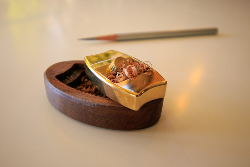 The Hovel pencil plane with its wooden stand, pencil shavings from sharpener