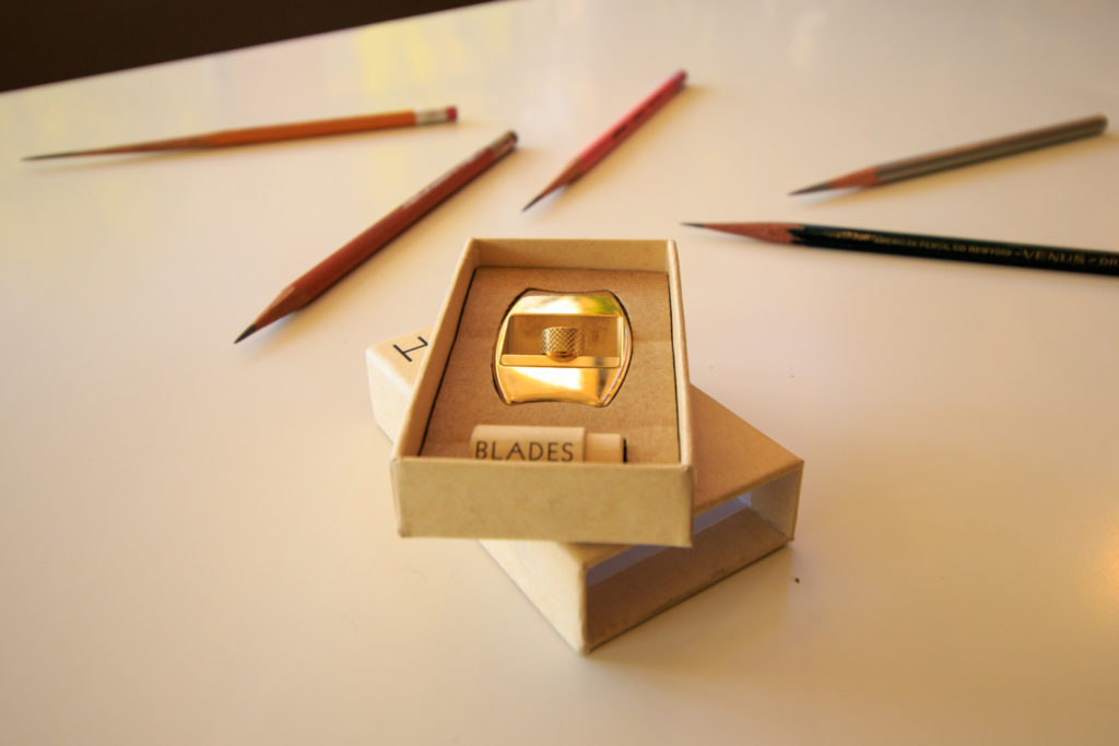 Hovel sharpener in fully recyclable box with blades, pencils surrounding box